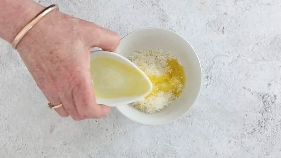 adding melted butter to panko breadcrumbs and parmesan cheese to make a topping for Cajun crab tarts