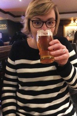 Charlotte boit une bière dans un pub lors d'un afterwork à Londres