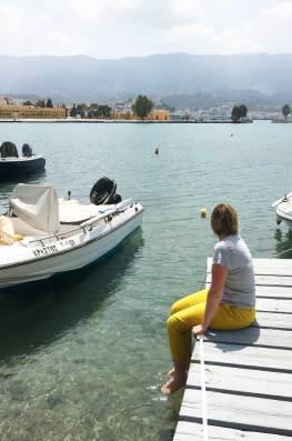 Charlotte assise sur un ponton les pieds dans l'eau transparente de Poros.