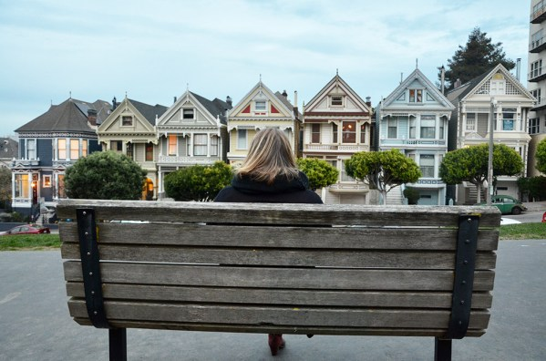Marie-Catherine de dos sur un banc du square Alamo, observant les Painted Ladies, San Francisco, USA
