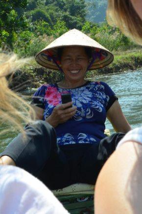Femme qui textote en ramant avec ses pieds, Tam Coc, Baie Along terrestre, Vietnam