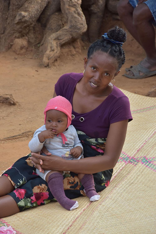 Femme assise sur une natte son bébé dans les bras, Madagascar
