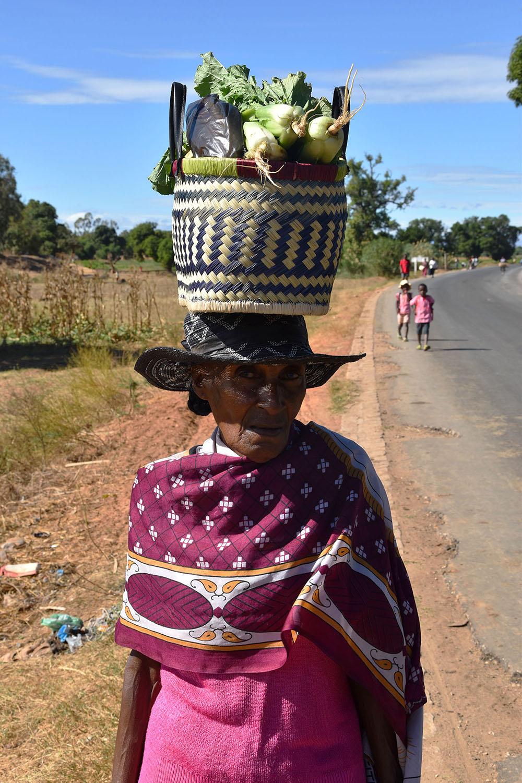 Femme qui pose avec un sac de légumes sur la tête, Madagascar