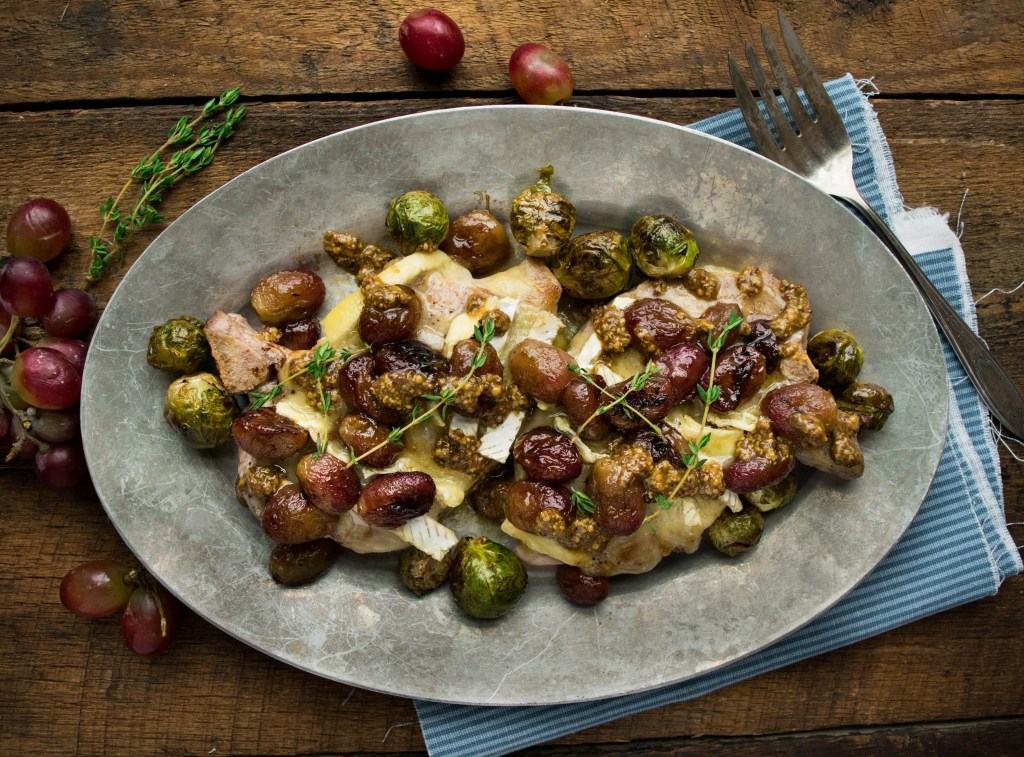 Brie Smothered Pork Chops with Roasted Grapes and Grainy Mustard Pan Sauce