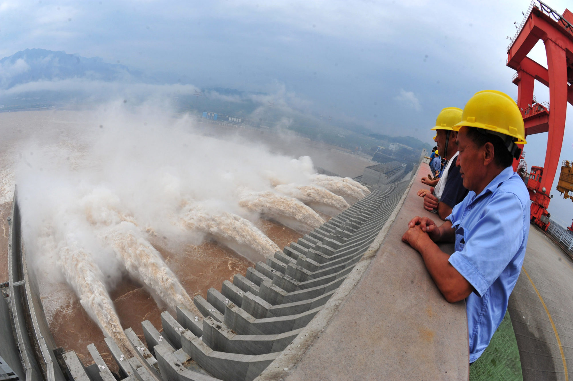 Chinese workers overlook polluted water from atop a dam; Blue Belt and Road