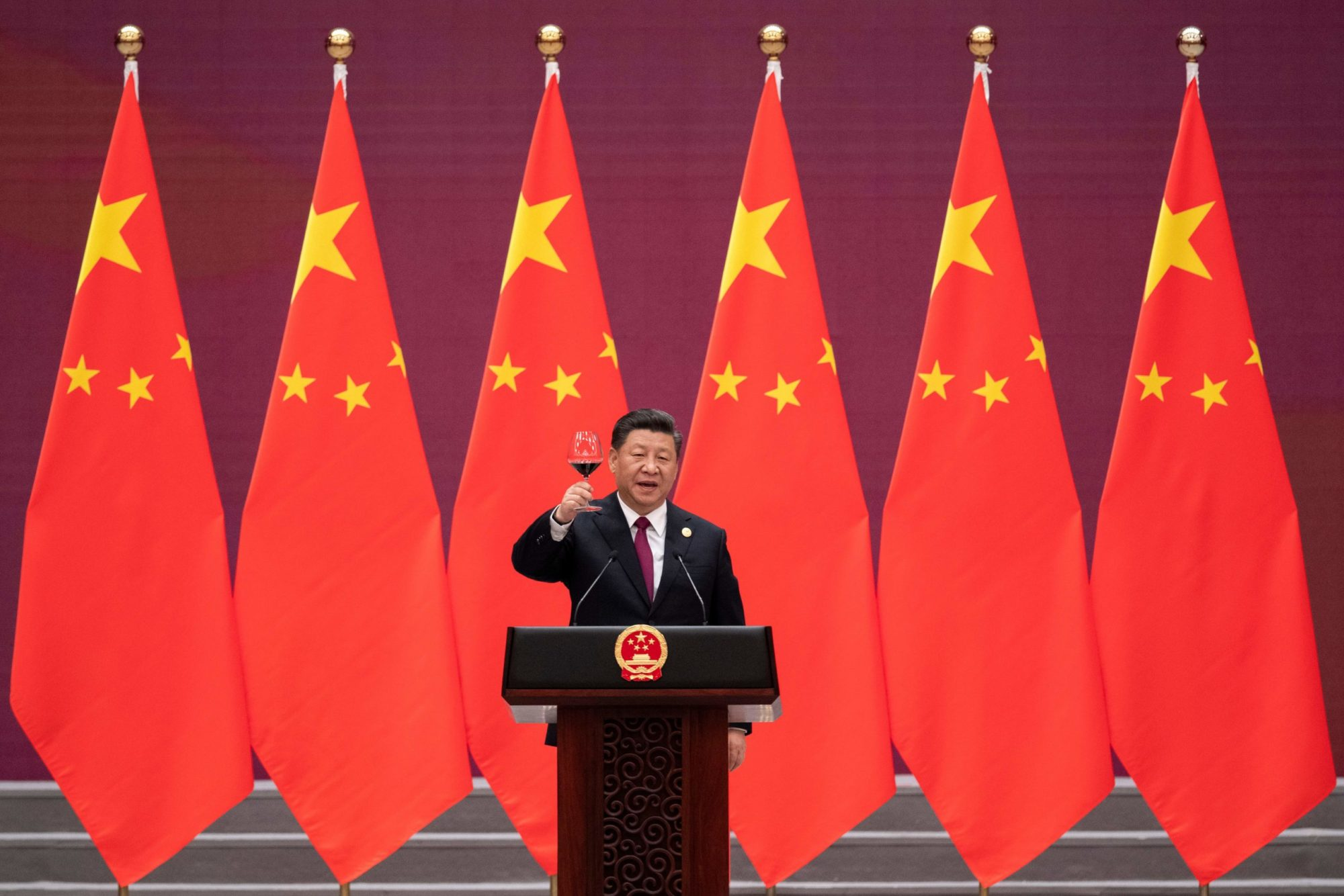 Xi Jinping cheers a glass of wine at a podium; ChinaPower
