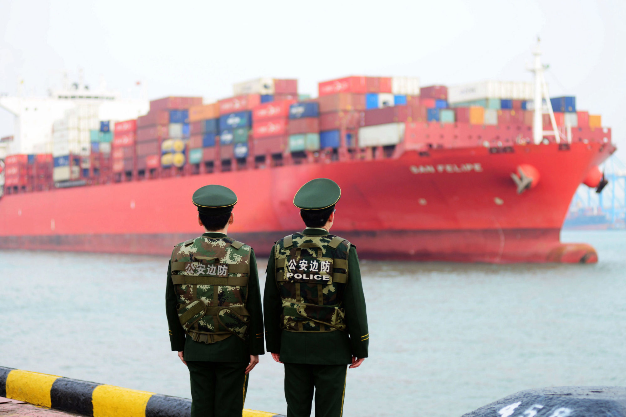 Two Chinese police officers watch a ship carrying freight containers in the distance; maritime silk road.