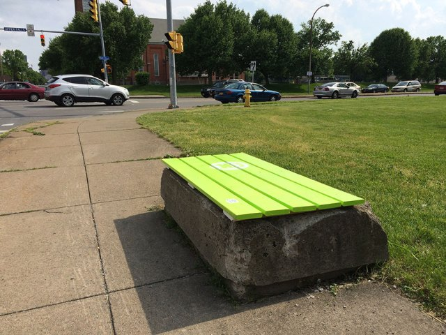 An old tree protector wall on Joseph Avenue, reborn as a bus stop bench.