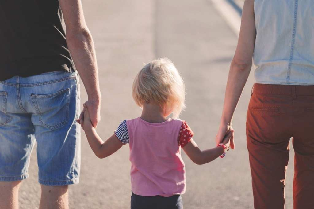 A child holding the hands of both her parents.
