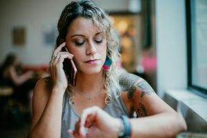 woman frowning and looking at watch while talking on the phone