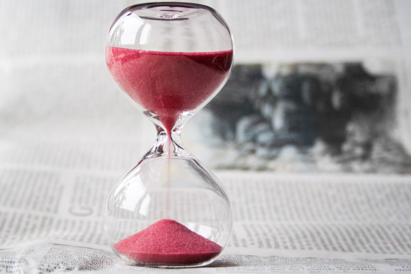 How to stop procrastinating - photo of hourglass sitting on a newspaper