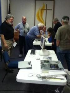 Members of the Monday Night Crew work on a sick Mac