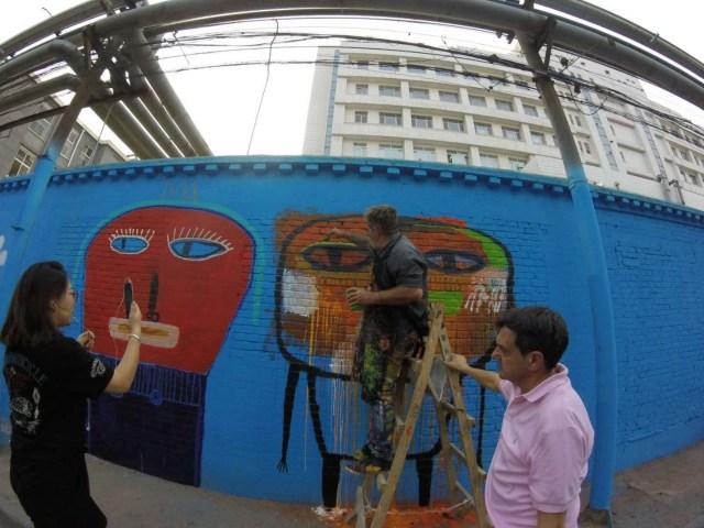Milo Lockett pintando el mural en una de las calles de Beijing.