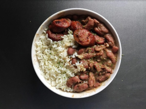 Bowl of red beans and rice with sliced smoked sausage