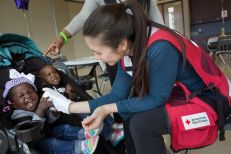 January 1, 2016 -- Garland, Texas -- ARC response to the tornados around Dallas, Texas. ARC volunteer Sara Hersey plays with shelter residents D'Kaelyn James, age 2 (the boy) and D'Andrea Rushing, age 1 (they are brother and sister). Photos by Dennis Drenner for the American Red Cross.