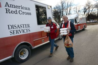 Missouri Floods. Red Cross volunteers John Lewis and George Muller carry hot meals to families during the flood relief effort in Arnold, Missouri. Photo by Daniel Cima for the American Red Cross