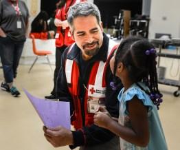 Shelter manager Carlos Ortiz takes a moment to chat with a child staying at the South Florence High School shelter. Photo by Virginia BEcker