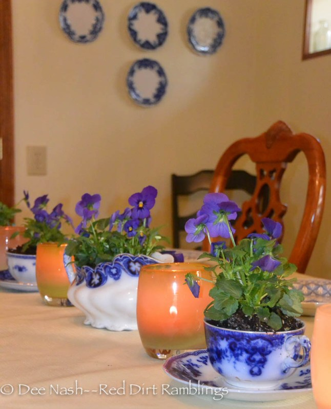 I planted violas in a flow blue china gravy boat and four teacups with saucers. Between them, I placed glassybaby candle holders.