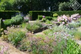 Gracious beds and borders in Sylvia's Garden. Small flowering plants give it a frothy appearance.