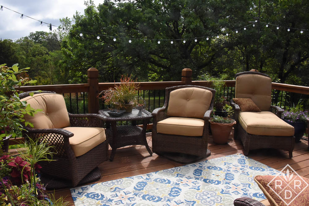 Deck with plants, chairs and rug. It's a cozy outdoor space where we relax in the evenings.