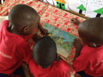 Nursery children eagerly sharing a book.