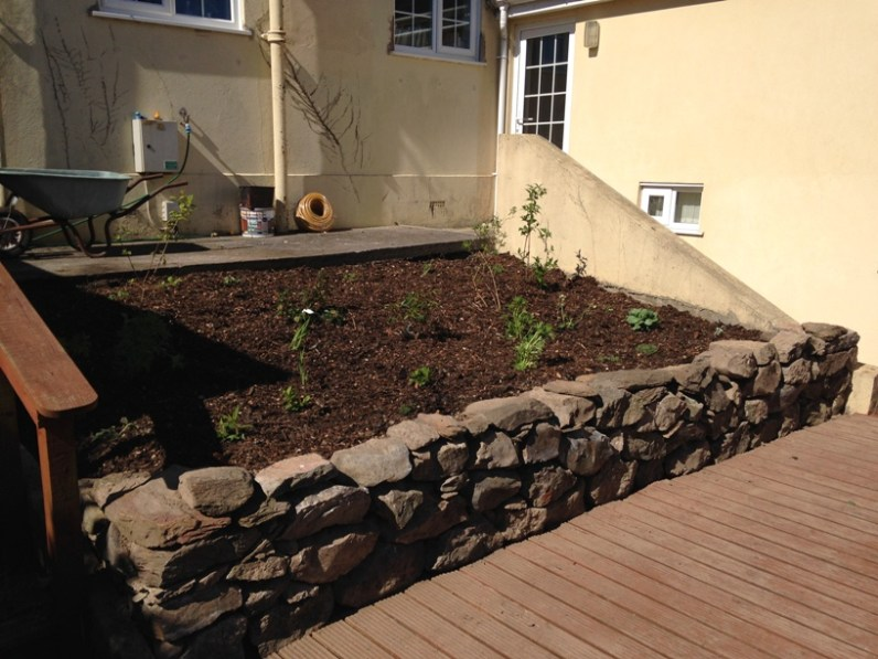 rebuilt srystone wall and replanted flower bed.