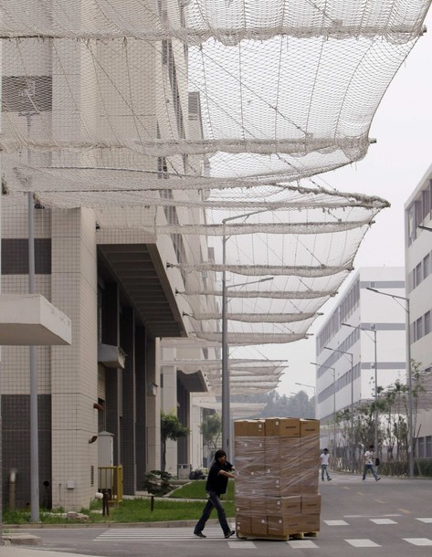A worker pushes a trolley carrying products under nets which are installed on a factory building to prevent workers from jumping to their deaths at a Foxconn factory in Langfang