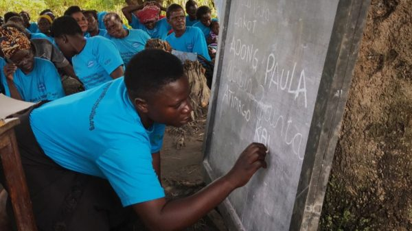 Happy borrower demonstrating her new skills by writing on chalkboard.