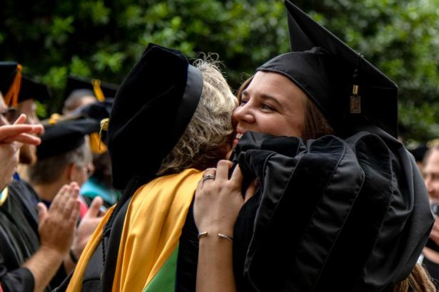 Professor and student embrace during commencement