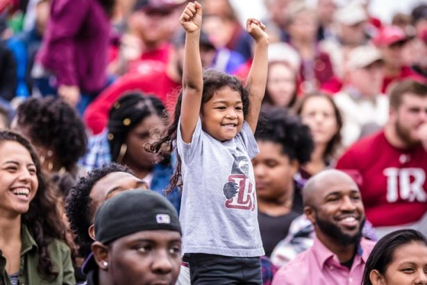Young fan cheers in stands at game