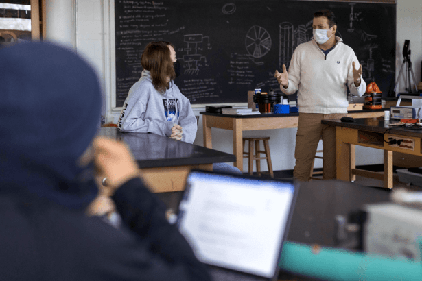 Professor talks with student in science lab while student in foreground works on computer