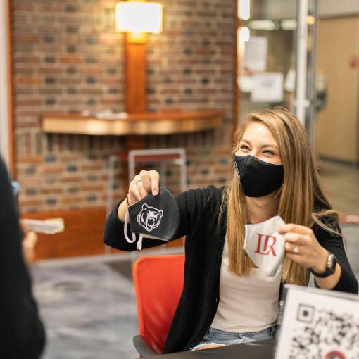 Student wearing a mask hands out masks at information table