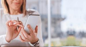 Mulher loira usando a conta digital triboo no celular