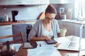 Mulher usando calculador para pagamento de contas