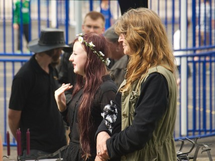 Two women with long hair stand next to blue railings. They are looking off to the left of the photographer. One has a garland of large daisies around her hair