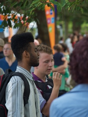 Two young men share a cigarette beneath trees in the park, surrounded by crowd