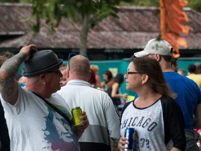 A woman in glasses and a man in a pork pie hat chat in the crowd by the main stage. They are framed from the waists up; he is drinking Ting and she is drinking lager