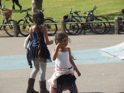 Two little girls in the skate park. One faces towards the camera and has a rainbow painted on her face. The other looks away from the camera towards a row of parked bicycles