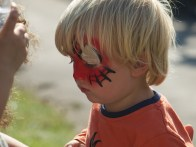 Close up of a blonde toddler with Spiderman face paint