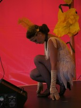A female dancer wearing a white fringed dress, long gold gloves and yellow feathered head band crouches down on stage in the cabaret tent