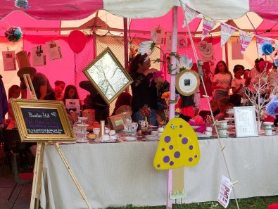 """The Bambini Hub arts and crafts tent, full of children making hats for a mad hatter's tea party. The tent is pink and white and there is a long table covered in teacups and knick knacks. A sign reads """"Come play with me!"""""""