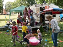 """Children play in front of the """"Bramble FM"""" stage in the kids area, which is made from a caravan. Two grown ups in party hats speak into microphones on the small stage"""