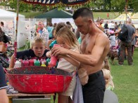 A man helps young children to squirt brightly coloured paint into a red bucket in the kids' area of the festival