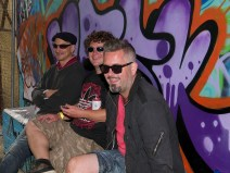 Three men sit backstage in sunglasses waiting to perform. They are all smiling at the camera and behind them is a concrete wall covered in large, colourful graffiti tags