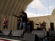 A band on the main stage. The singer at the front waves his arm as he sings and has closed his eyes. Behind him are saxophonist, drummer, guitar and bass