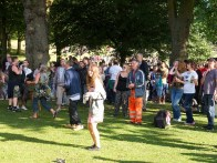 A crowd of revellers of all ages enjoys the shade of the trees while watching the show. A teenage girl dances in the foreground