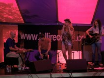 Elles Bailey sings on the market stage. She is backed by men playing acoustic guitar, keys and cajon. Pink light comes through the tent