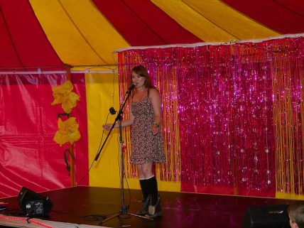 A woman in a flowery dress speaks into the microphone in the cabaret tent. The tent is pink and yellow striped and behind her are giant flowers and a glitter curtain