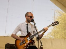 The 45s bassist plays on the main stage wearing a white shirt, thin black tie and sunglasses