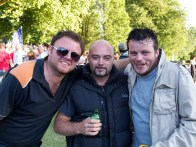 Three men holding beer grin at the camera with their arms around one another. There are trees behind
